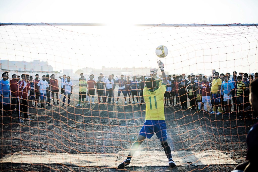 Dressed in soccer jerseys from around the world, the workers are spending, their only weekly day off, on their own soccer tournament. However, it's on a court without grass and air conditioning.