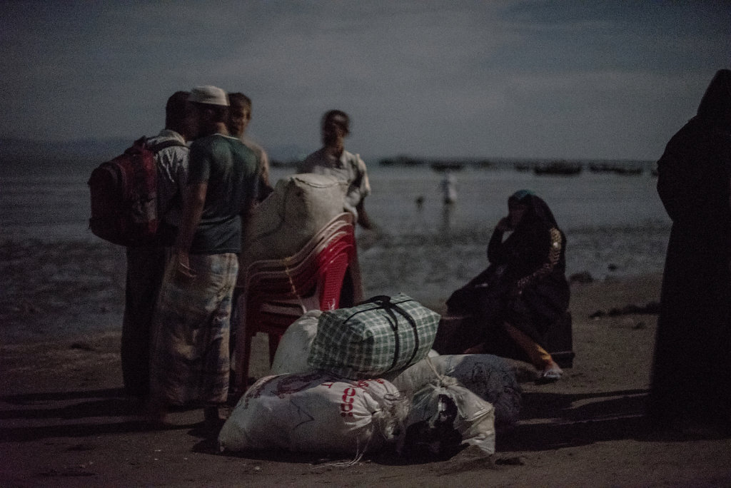 A family rests after arriving on safe ground, at Shahpuree island, Bangladesh
