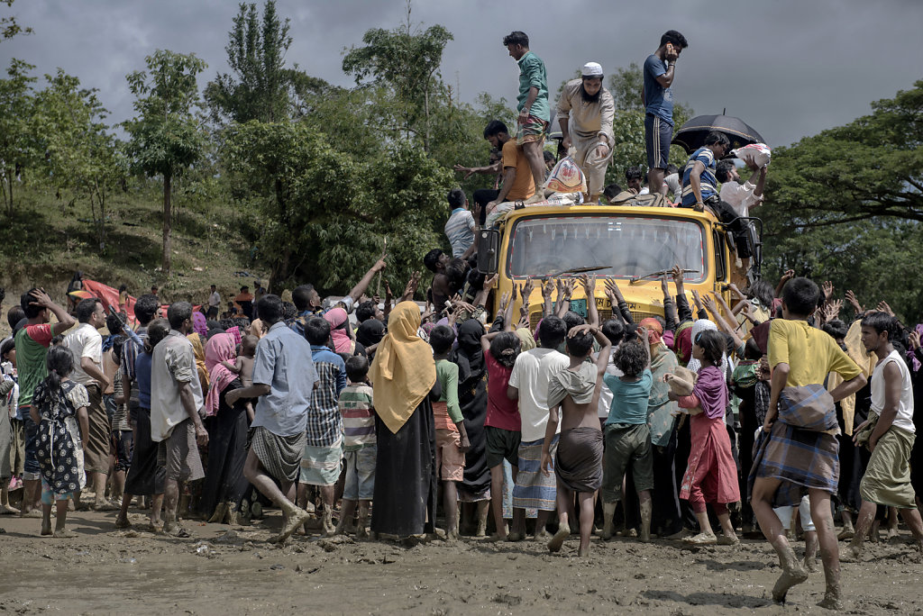 On a muddy area in the outskirts of Kutupalong refugee camp, aid trucks come a couple a times a day, to hand out food and clothe.  But they don't have enough to satisfy the high number of refugees, who only have this opportunity for food.